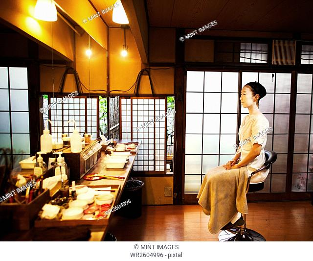 A woman seated on a stool in front of a mirror, a geisha to be made up in the traditional style
