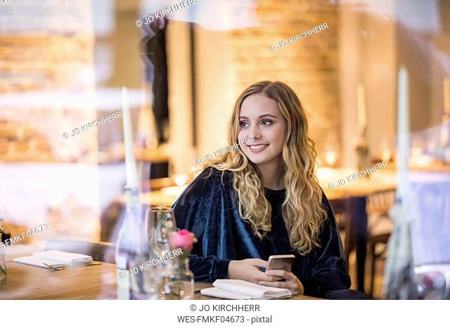 Portrait of smiling young woman waiting in a restaurant