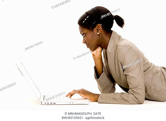 a young black woman using a laptop on the floor