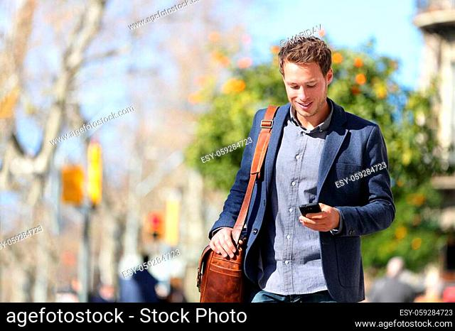 Young urban businessman professional on smartphone walking in street using mobile phone app texting sms message on smartphone wearing smart casual jacket