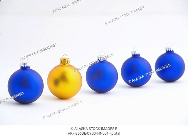 Four blue Christmas tree balls stand in line with one gold ball near front
