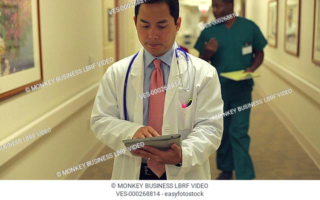 Male doctor walking along hospital corridor looking at notes on digital tablet.Shot on Sony FS700 in PAL format at a frame rate of 25fps