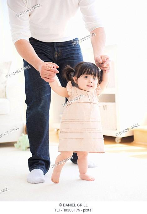 Father helping baby daughter 12-17 months with her firsts steps