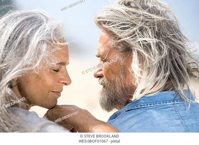 Affectionate senior couple looking into each others eyes in front of the sea