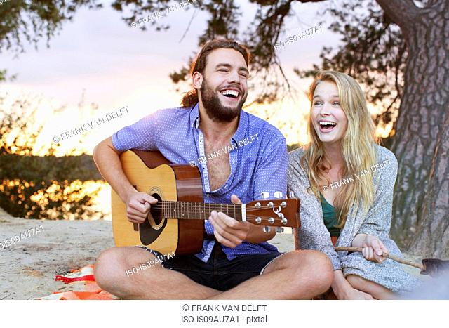 Young couple playing guitar by lake