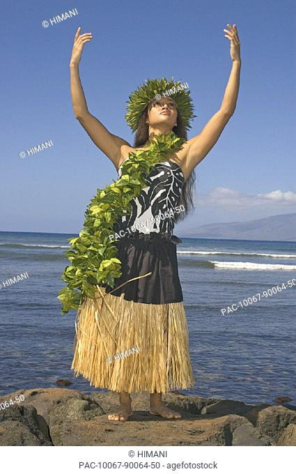Hula dancer with haku lei in traditional outfit on rocky coast, ocean background