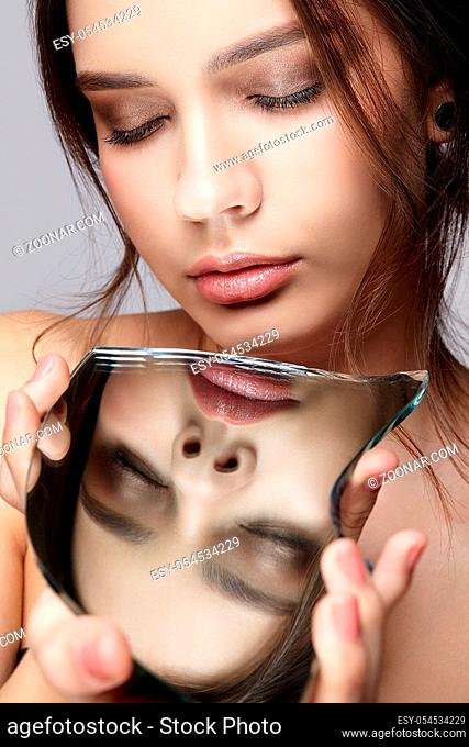 Girl with a shard of the mirror. Female with mirror shard in hand posing on gray background. Face reflection in mirror splinter. Eyes closed