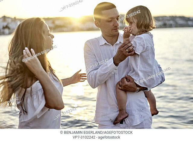 candid family, unposed, real people, sunset, at beach, seaside. In Chersonissos, Crete, Greece