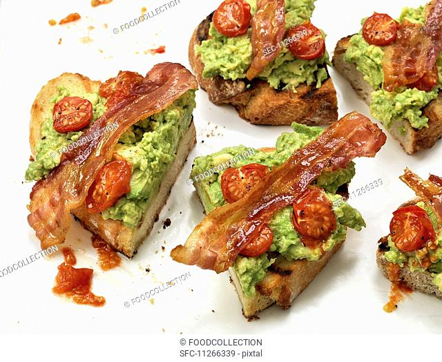Toast topped with bacon, guacamole and tomatoes