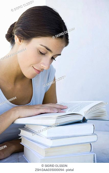 Woman reading stack of books