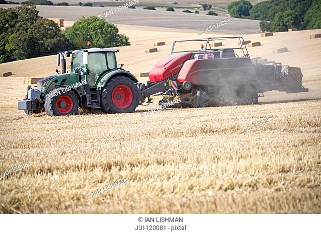 Tractor baler making straw bales in field after summer wheat harvest on farm