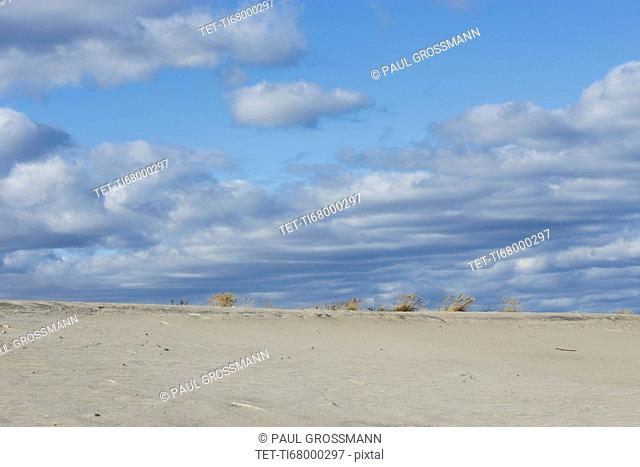 Clouds over sand dunes on beach