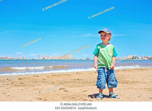 Cute small boy standing on the beach near Mar Menor sea, Spain