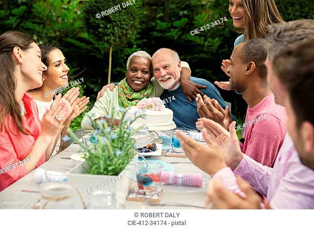 Affectionate multi-ethnic senior couple hugging celebrating anniversary at patio table
