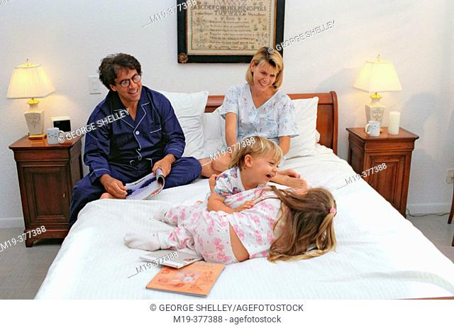 playful family on a bed