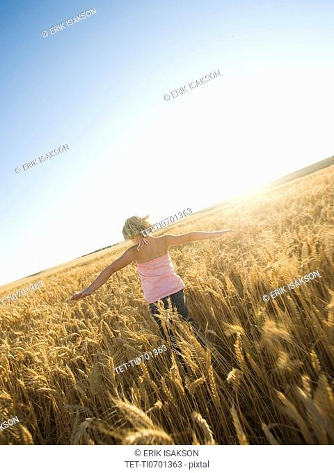 Girl running through tall wheat field
