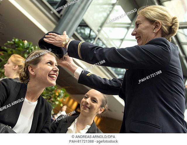 Attendant Stefanie Krallmann (r) places a Lufthansa head piece on applicant Liane Fleischhauer (19, Hockenheim) in the waiting area of the casting session in...