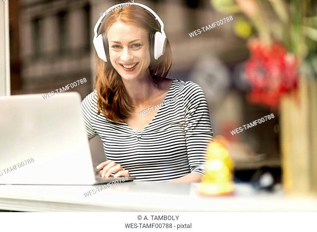 Portrait of smiling woman sitting in a coffee shop using headphones and laptop