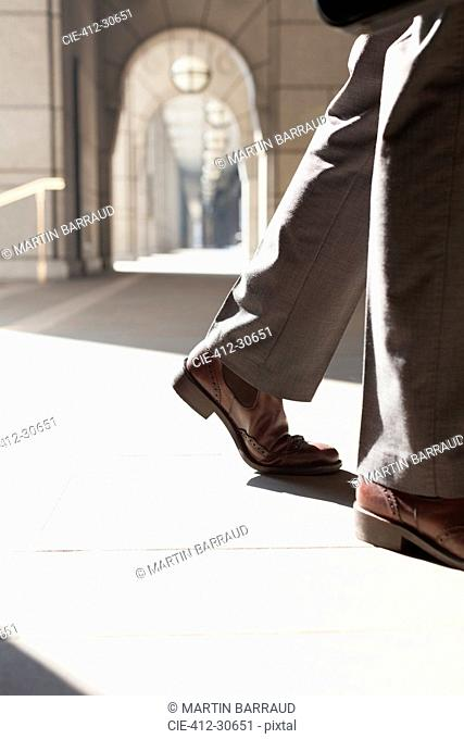 Feet of corporate businessman walking in sunny cloister