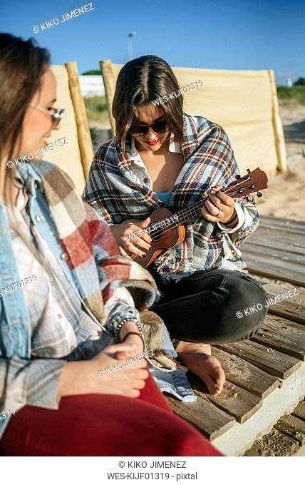 Woman playing ukulele on the beach while her friend watching her
