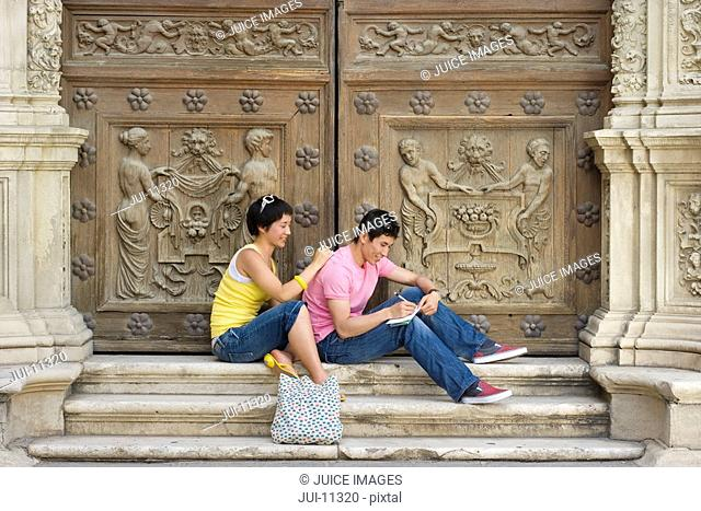 Couple on steps by wooden doors writing, smiling, side view