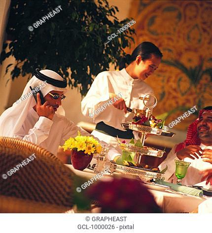 Waitress serving lunch to Arab businessmen