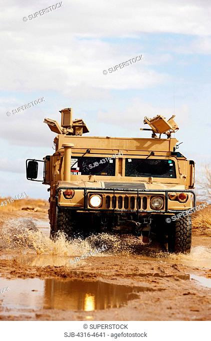 HMMW, or Humvee, drives through puddles of water on a muddy road in Afghanistan's Helmand Province