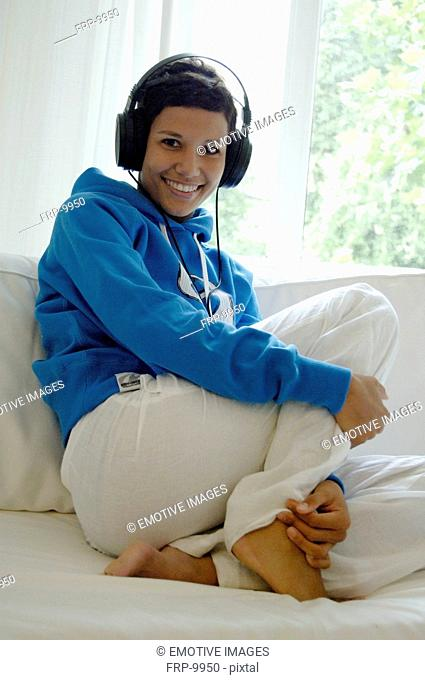 Young woman listening to music on couch