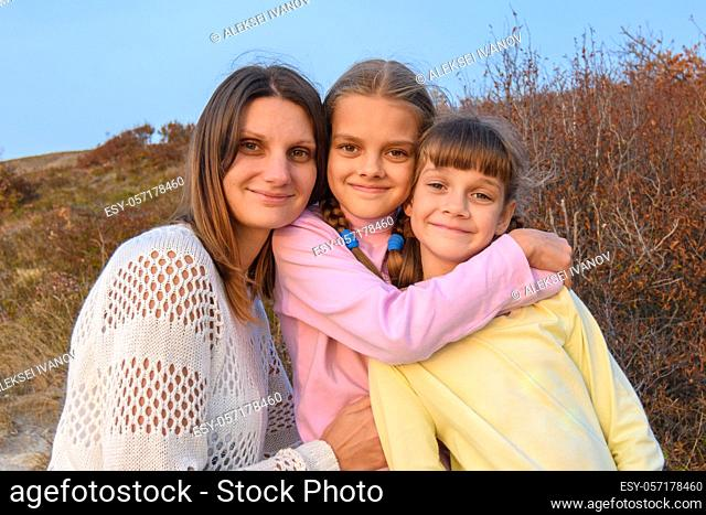 Portrait of a happy girl with two daughters on the background of nature