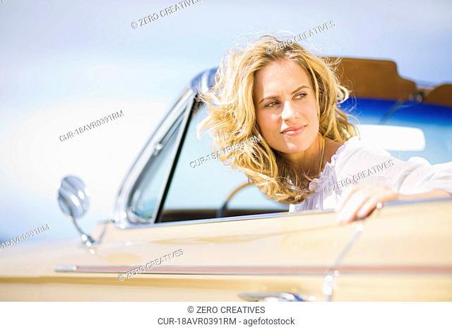 Blond woman, classic convertible, blue sky