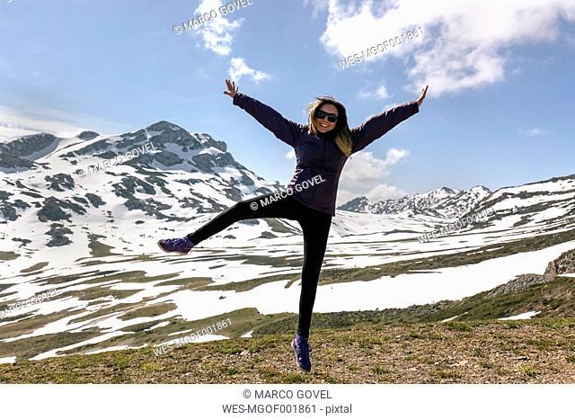 Spain, Asturias, Somiedo, playful woman jumping in mountains