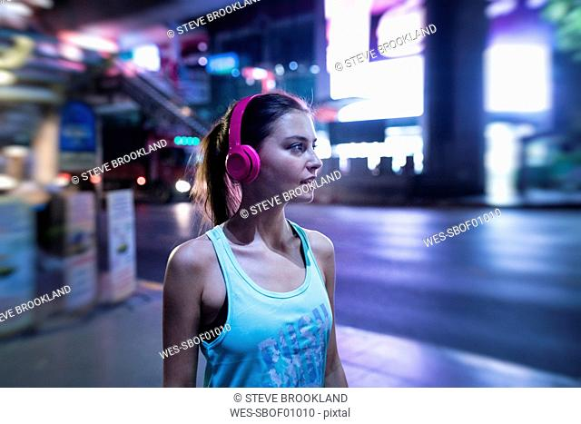 Young woman in pink sportshirt in modern urban setting at night