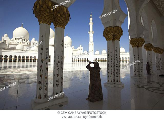 Visitor taking photos between the gilded columns of Sheikh Zayed Bin Sultan Al Nahyan Mosque, Abu Dhabi, United Arab Emirates, Middle East