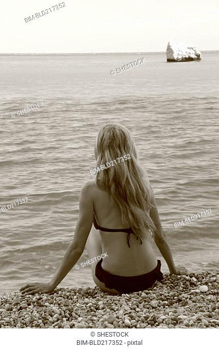 Caucasian woman sitting on rocky beach