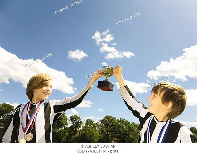 Boy footballers with medals and trophy