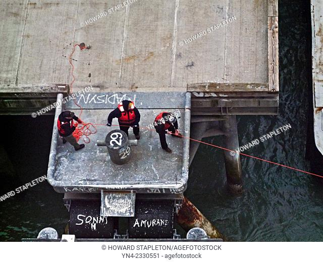 Dock workers secure a ship's line to a pier in Alasla