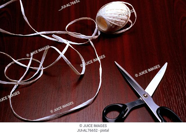 High angle view of a pair of scissors and ribbon