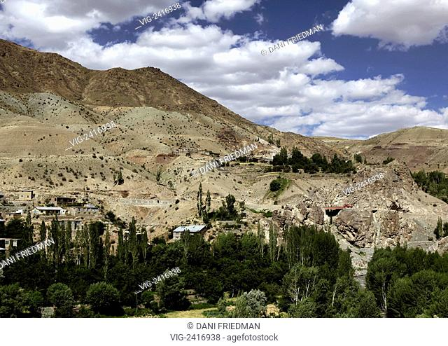 A remote village rests at the base of a large mountain in the Kargil District by the Srinagar-Leh Highway. - JAMMU AND KASHMIR, INDIA, 10/07/2010
