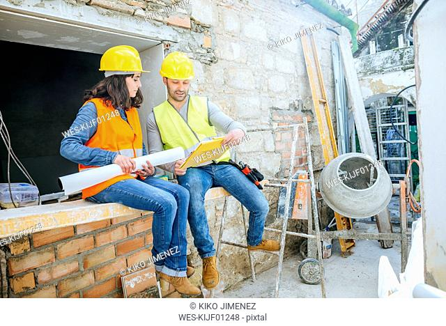 Male and female construction worker talking construction site