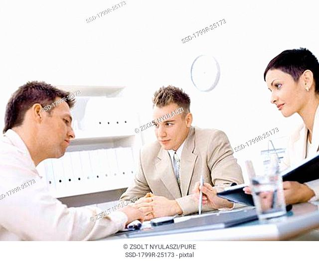 Businessman and a businesswoman interviewing a mid adult man