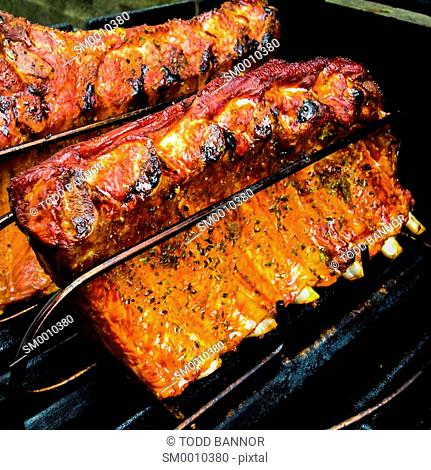 Barbecue Baby back ribs, seasoned and smoking on grill