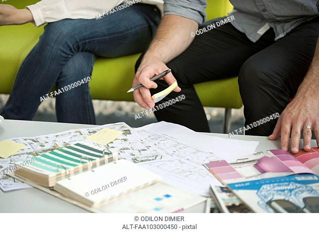 Man and woman looking at paint swatches and blueprints, cropped