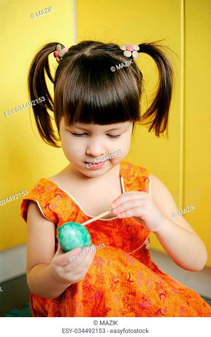 little Girl paint easter eggs in yellow background. Adorable little girl coloring an Easter egg