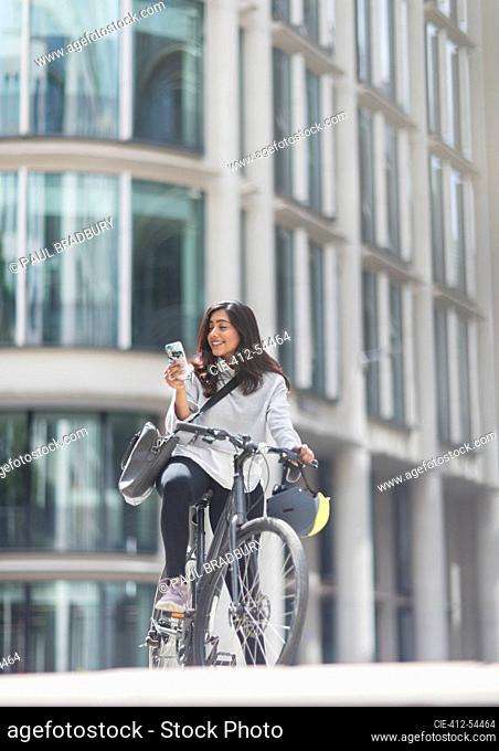Woman using smart phone on bicycle in city