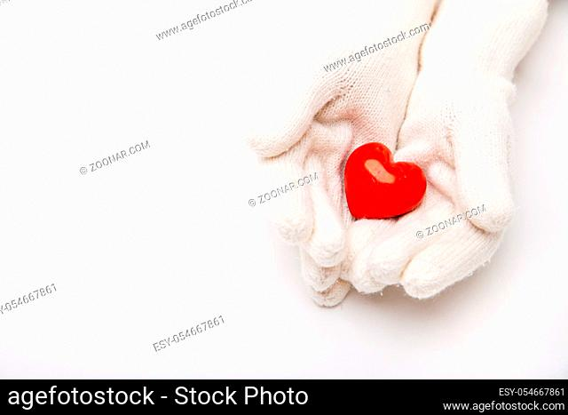 Woman hands in white gloves holding red heart symbol