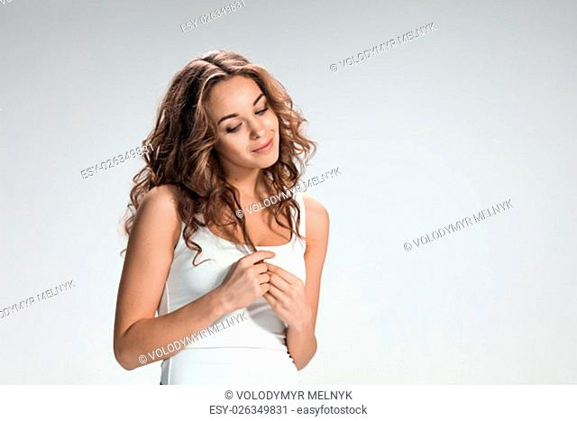 The young woman's portrait with shy emotions on gray background
