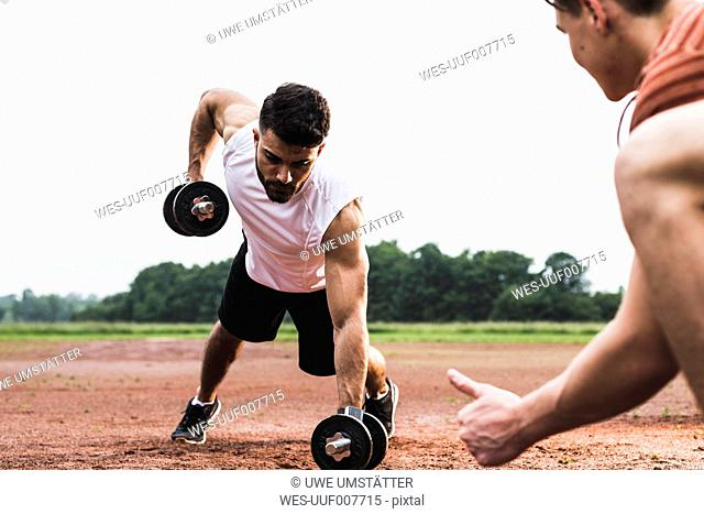 Athlete exercising with dumbbells on sports field supported by his training partner