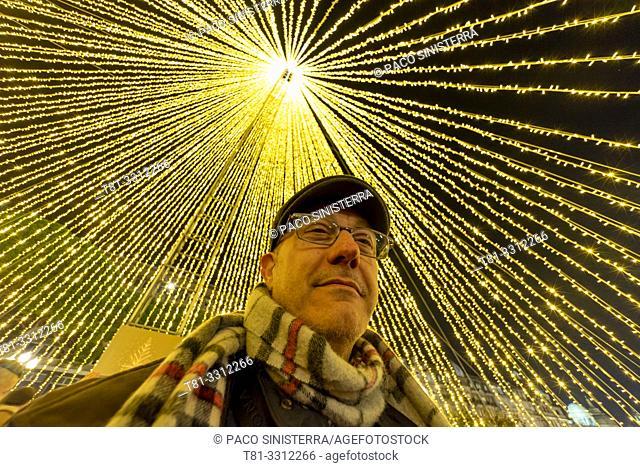 Man under christmas lights. Portugal