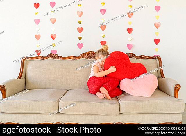 Young blond girl on couch hugging big red plush pillow indoors couch