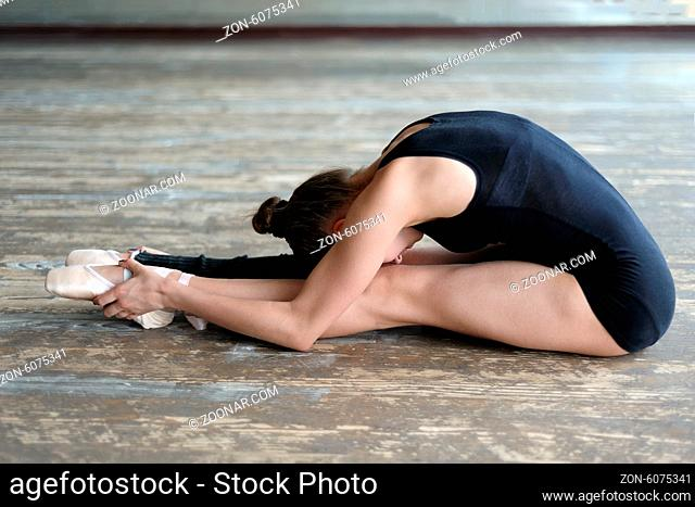 Young ballerina making stretching exercise sitting on the floor in the studio
